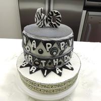 Black And White 60Th Birthday Cake Vanilla cake layered with apricot jam and coconut and covered in soft fondant.