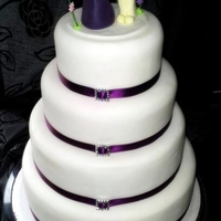 Purple And White Wedding Cake 4 tier purple and white Wedding cake with a topper of the bride and groom. Thanks for looking