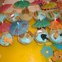 Summer Beach Cupcakes   made these blue cupcakes with blue frosting and topped them with diff. candies and teddy grahams then topped off with mini umbrellas.