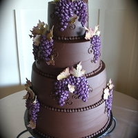 Chocolate Ganache Wedding Cake Chocolate Ganache covered Wedding Cake with buttercream grapes. Grape leaves were made out of marbled colored gumpaste and dusted with...