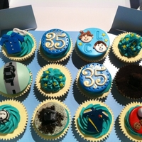 Customised Birthday Cupcakes Custom cupcakes for a 35 year old man. Toppers include turf (peat), his children, GAA jersey, cookies and milk, his car, his work clothes,...