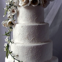 White Floral Wedding Cake   gum paste flowers on a white fondant tiered cake with stenciled details