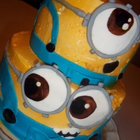 Minions!!! 2 tiered yellow cake, filled and frosted with buttercream, air brushed yellow and detailed with fondant