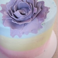 Pastel Triple layer cake, filled and frosted with buttercream, with a gumpaste flower