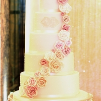 Pearl Piped Rose Cascade 5 tier cake with pearl detail. Cascading gumpaste roses in blush, vintage pink, ivory and white. Monogram plaque with my and the couples...