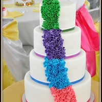 Rainbow Ruffle Wedding Cake A 4 tier rainbow ruffle cake. Each tier had the same rainbow color. The colors were chosen to match the bridesmaids dresses.