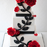 Red Rose Wedding Cake Three tier square wedding cake with handmade sugar roses. The black vine with leaves was made using fondant.