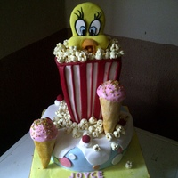 I Tnk I Taw A Puddy Tat! tweety bird popping out of a popcorn bag,hiding away from puddy tat.......8 inch sponge cake sculpted to form the popcorn bag,tweety head...