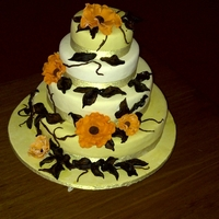 Simple Open Rose Wedding Cake sugar flowers and leaves,brown paste anf prim rose and orange colours,four tier cake covered in fondant.