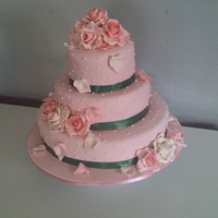 Subtle Passion three tier fruit cake,covered in fondant, gumpaste roses and petals in pastel shades, dark green ribbon.