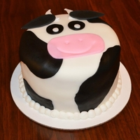 Cow Cake   cake is fondant, black spots are fondant, horns and ears are made out of gumpaste and boarder is bc.