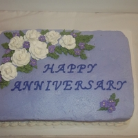 Lavender Anniversary Cake Chocolate cake with raspberry filling, iced with lavender buttercream, gum paste white roses and purple violets, and buttercream leaves.
