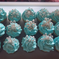 Snowflake Cupcakes Royal icing snowflakes and edible glitter on chocolate cupcakes with blue buttercream icing.