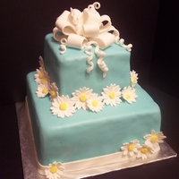 Daisy Tiered Cake Alternating chocolate and vanilla cake layers with vanilla buttercream icing. Covered in light teal-colored fondant. Bow and daisies are...