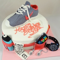 Marathon Runner's Cake Waist belt with water bottle, pace band, ipod, energy gel, and runner's watch with running shoe on top. Red Velvet cake with Cream...