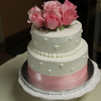60Th Anniversary Cake   White cake with raspberry filling. Covered in buttercream and topped with fresh pink roses