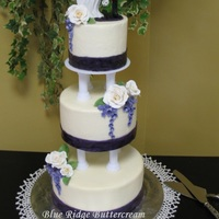 "White Rose And Wisteria Wedding Cake White butter cakes (5"", 7"", 9"") with vanilla American buttercream and raspberry filling. Decorated with fondant ribbons,..."