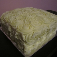 First Time Rosette Cake 4-layer lemon cake with rasberry and lemon buttercream filling. Rosettes are white ganache.
