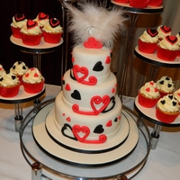 Best Of Both 3 tier wedding cake surrounded by cupcakes on a peacock fan style stand