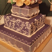 Covered In A Purple Fondant With Royal Icing String Work And Royal Icing Scrolls   Covered in a purple fondant, with royal icing string work and royal icing scrolls.