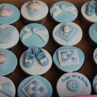 Baby Boy Cupcakes Chocolate sponge cupcakes, choco late butter icing topped with sugarpaste baby item