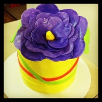 Purple Flower Cake Bright Purple Flower, pastel yellow base. 6 inch cake. Flower is gumpaste. Covered in MMF.