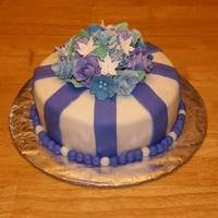 Blue Gumpaste Flowers Blue Velvet Cake covered in Fondant with Blue Stripes and Blue Gumpaste Flowers.