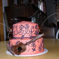 Notes Of Paisly a yellow cherrie chip cake,covered in red buttercream. hand piped black paisly. and fondant cowboy boots, microphone, and music notes also...