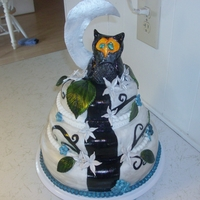 A Three Tier Owel Themed Birthday Cake. Its Colors Are Silver,blue, And Black. It Has Fondant And Gum Paste Accents.