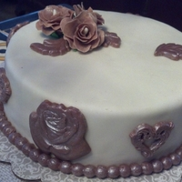 Chocolate Fondant Medallions And Roses  This is my first cake with homemade chocolate fondant. I dusted everything with pearl dust and it changed the color to the look of copper...