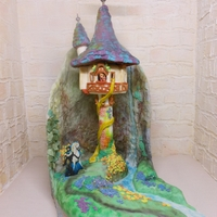 "Lit-Up Tangled Rapunzel Tower Cake Tangled Rapunzel tower cake with tower that lights up. It stand at 24"" tall with hand cut cake board and back drop. The cliffs are..."