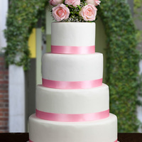 Romantic Pink And White Dummy wedding cake for my website. 4 Tier white cake with pink satin ribbon and silk rose topper.