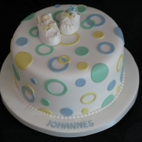 Polkadots And Baby Shoe Chocolate pound cake with chocolate ganache filling covered with white fondant, polkadots and a gumpaste baby in a shoe.