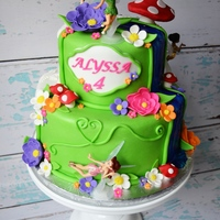 "Two Sided Tinkerbell Cake 10"" & 6"" Chocolate cake with vanilla buttercream covered in fondant. All of the flowers and accents are edible except for the..."