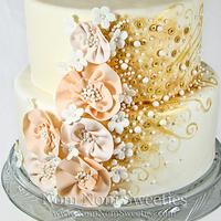 "Fashion Inspired Wedding Cake A fashion inspired wedding cake with sugar ""fabric"" flowers, blossoms, pearls and gold sequins and a design in gold."