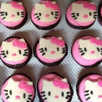 Hello Kitty Cupcakes Chocolate Cupcakes with Vanilla Buttercream Frosting tinted pink. Hello Kitty is hand cut out of fondant with royal icing for face details...