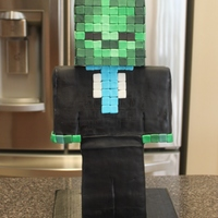 Minecraft Zombie Cake 1 1/2 feet tall. Body is cake and the head is a 5x5 faux tier. The head took 320 fondant squares.