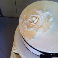 Black And White With Rose   Cake: buttercream frosting, white gumpaste rose and black ribbons Cupcakes: black wrappers, white buttercream frosting, white roses