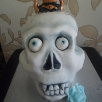 Skull Cake   spong cake with vanilla buttercream carved into a skull and decorated with eyes a dagger and a blue rose.