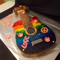 3D Guitar Cake Cake is iced in buttercream and hand painted with fondant accents. The inside of the guitar is red and orange marbled cake!
