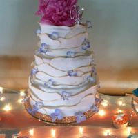 Wedding Cake Three tiered cake with fondant decoration and gold luster dust. Real flowers