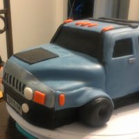 Hummer Chocolate cake covered in grey-blue and black fondant. Tires are gumpaste covered in black fondant.