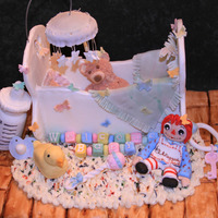 Cradle And All! This is a baby shower cake made of chocolate cake covered in fondant (floor), butter cream shag baby rug, fondant and gum paste: Raggedy...