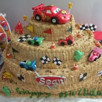 Cars 2 Cake Lightning Mc queen made out of rice crispies and covered with MMF. with race cars along the side of a three tier mocha cake