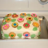 Flower Cookie Cake Flower-shaped cookies with hole in the center were iced and placed on cake with a peanut butter M&M in the center and spearmint leaves...