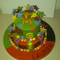 Simba Lion King Theme 2 layers, fondant simba on top surrounded by colourful swirls and stars with diamond and paw print on bottom layer.