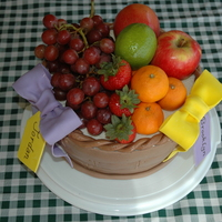 Fruit Basket Real fruit tops an Oreo cake covered with BC and MMF decos, for two sisters' birthdays.