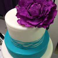 Large Purple Peony, Teal Ribbons A 10 in double barrel, 8 in half barrel, and 6 in round cake with an offset purple peony.