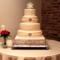 Winter Wonderland Round 4 tier fondant wedding cake, adorned with gumpaste snowflakes and rhinestone snowflake brooches.