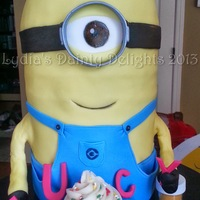 "Happy Birthday Minion Minion cake is 8"" round cakes stacked with the half round ball cake pan on top. Fondant covered cake with a vanilla cupcake."